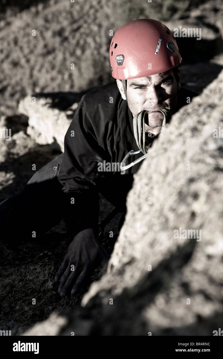 A rock climber looking towards the bolt with a quick draw in his mouth. - Stock Image