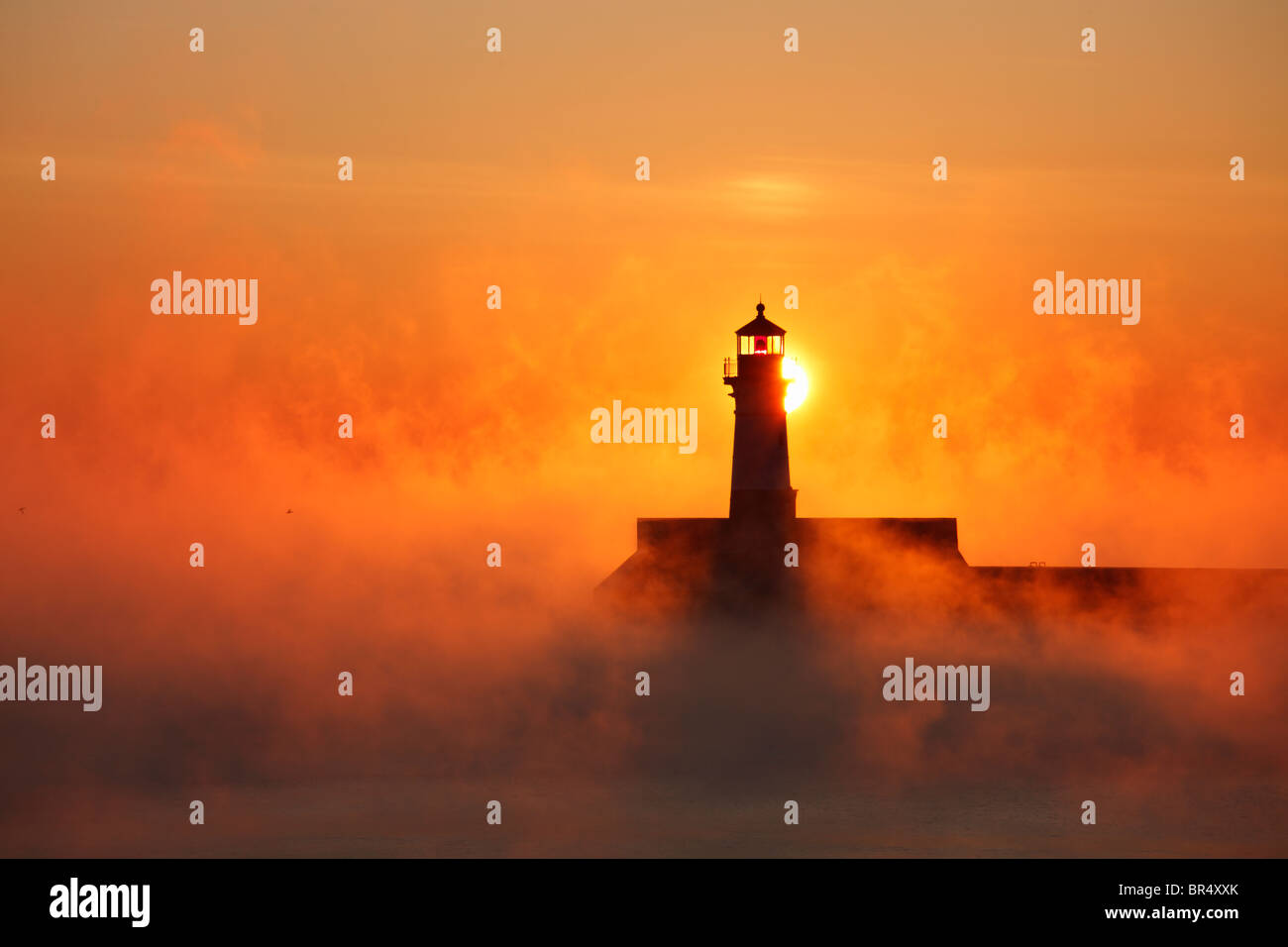 The sun rises behind the north pier lighthouse on Lake Superior in Duluth, Minnesota on a subzero (F) winter morning. - Stock Image