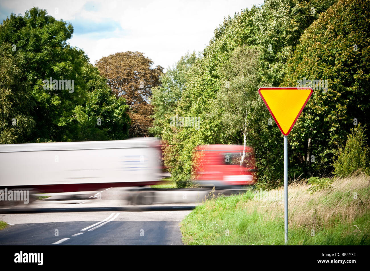 yield sign near crossroad and rushing truck - Stock Image