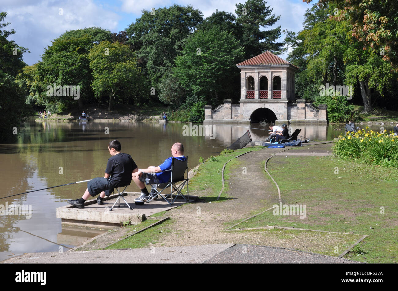 Fishing by the Birkenhead Park boathouse - Stock Image