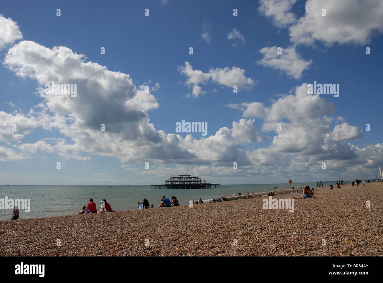 Brighton's stony beach on a sunny day and the ruined pier in the background with fluffy clouds - Stock Image