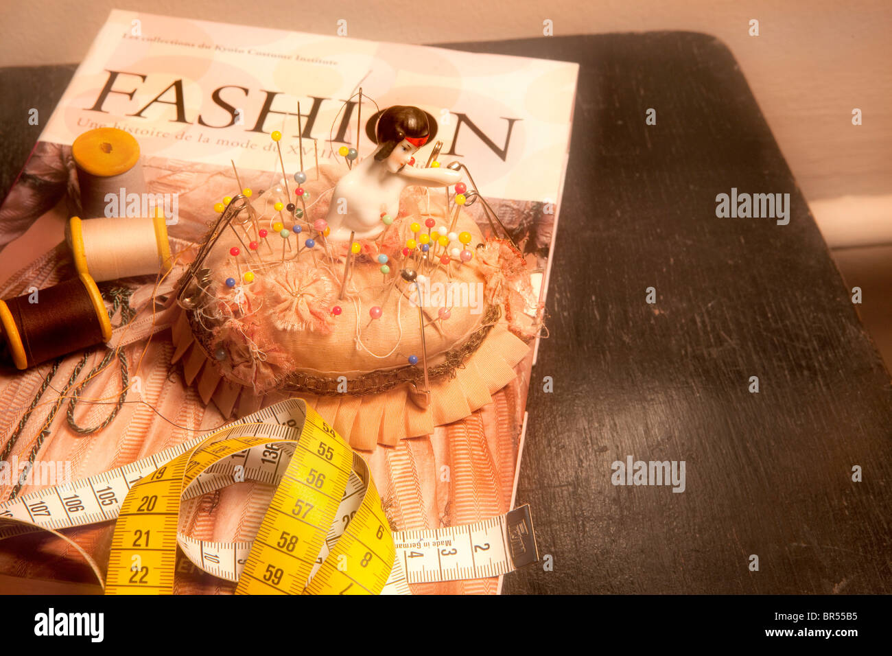 Fashion book, thread and pincushion with pins - Stock Image
