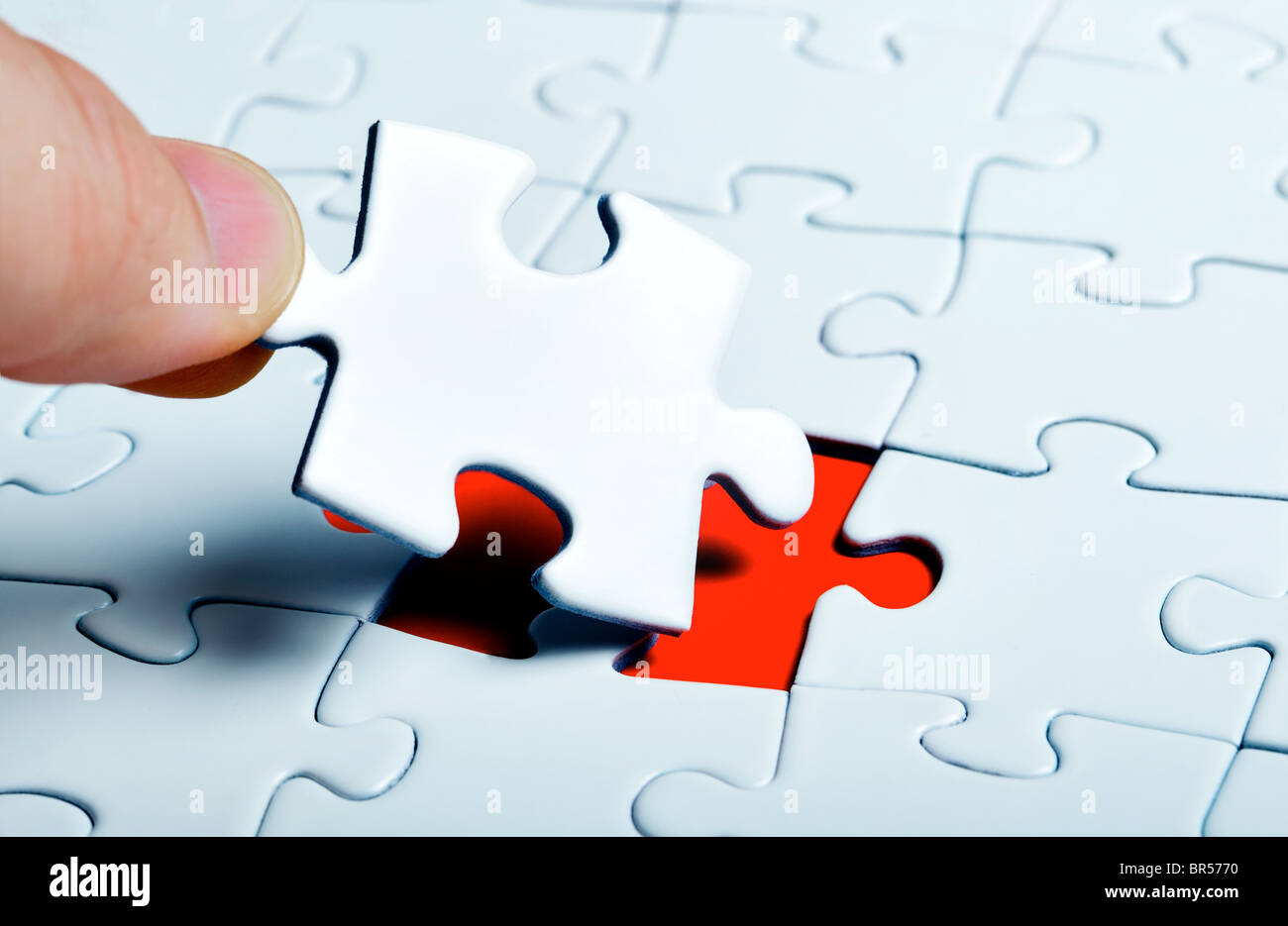 puzzle piece coming down into it's place - Stock Image