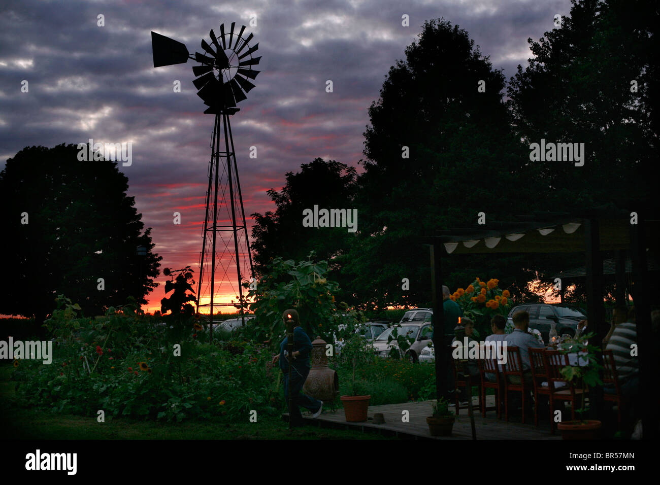 A large group eating outdoors at sunset on a rural farm with a windmill in the background. - Stock Image