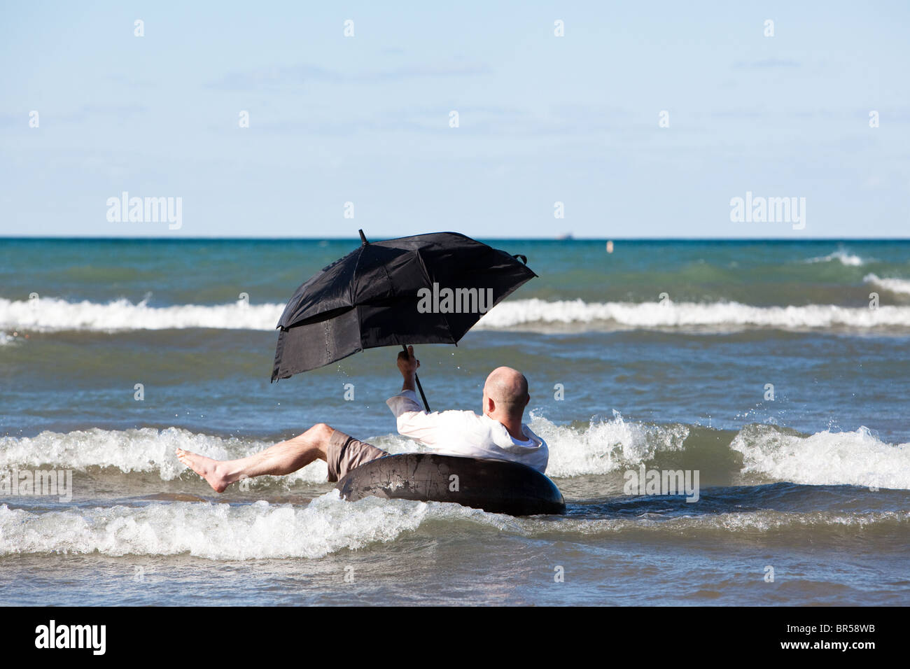 A Man travels with umbrella - Stock Image