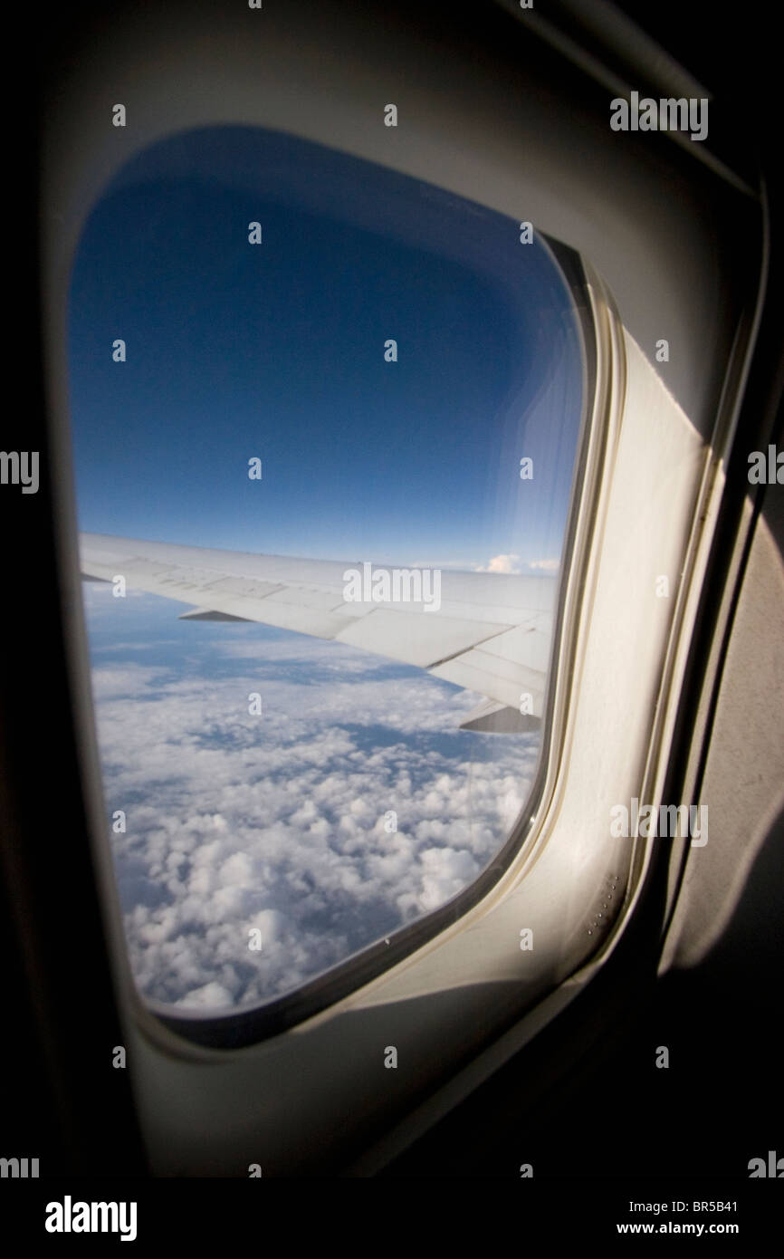 Airplane window view of clouds and sky - Stock Image