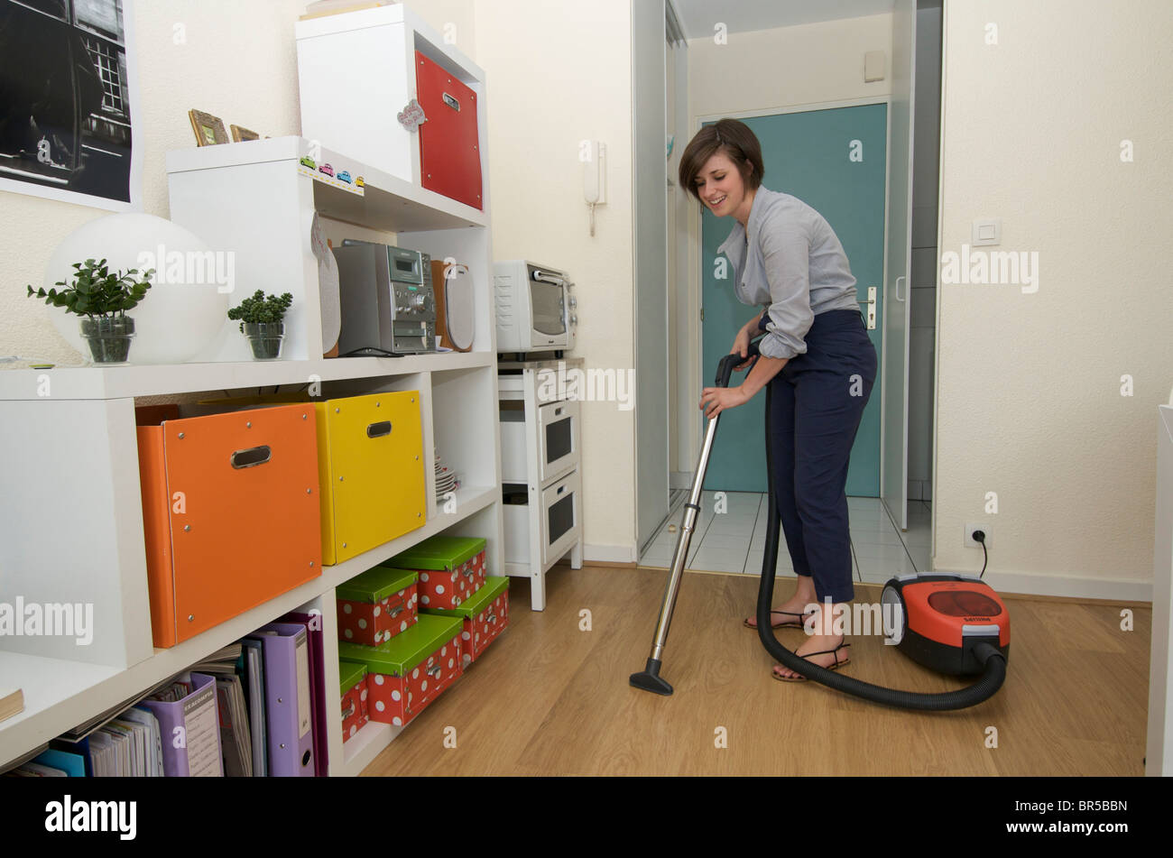 Young woman doing housework cleaning with a vacuum cleaner - Stock Image