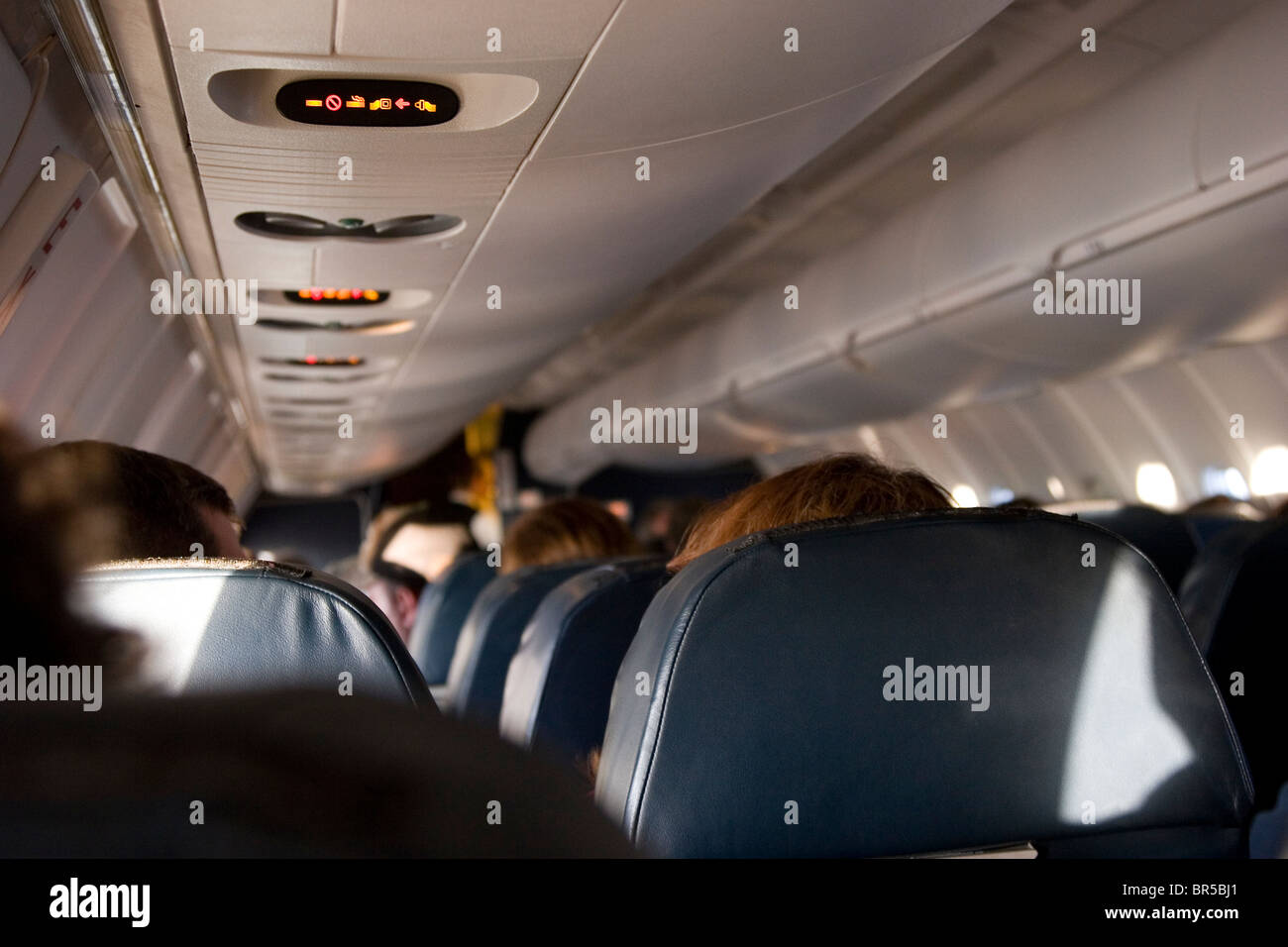 Airplane interior with rows of seated airline passengers - Stock Image