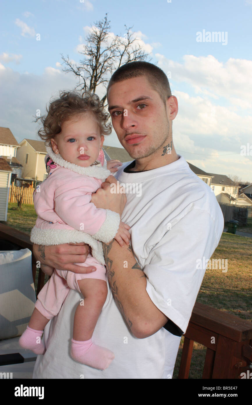 Proud Young Father With Tattoos Holds His Baby Daughter Stock Photo