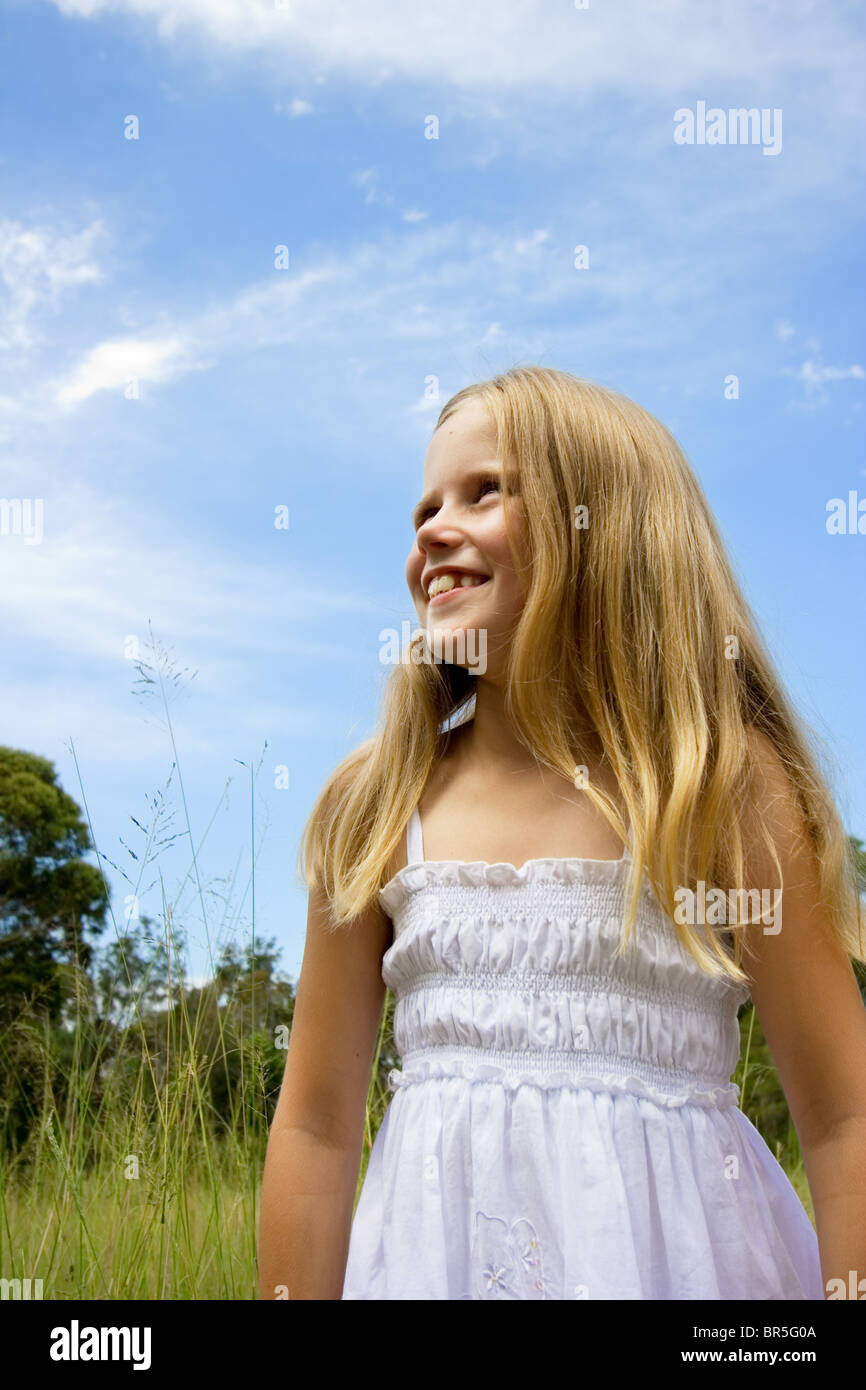 Little girl smiling and standing in a field against a blue sky Stock Photo