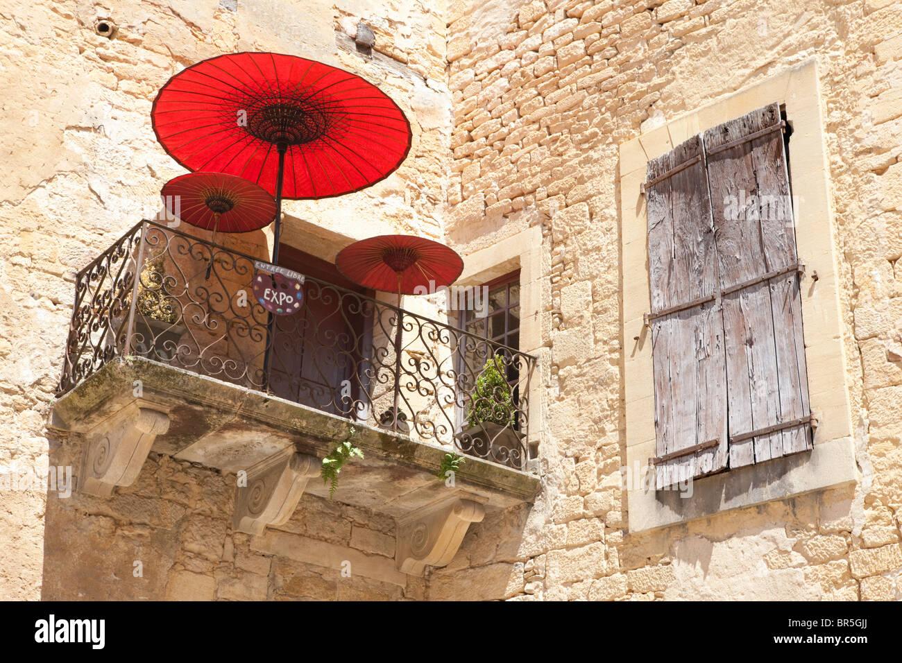 Red parasol on balcony, Sarlat-la-Caneda; Dordogne; France - Stock Image