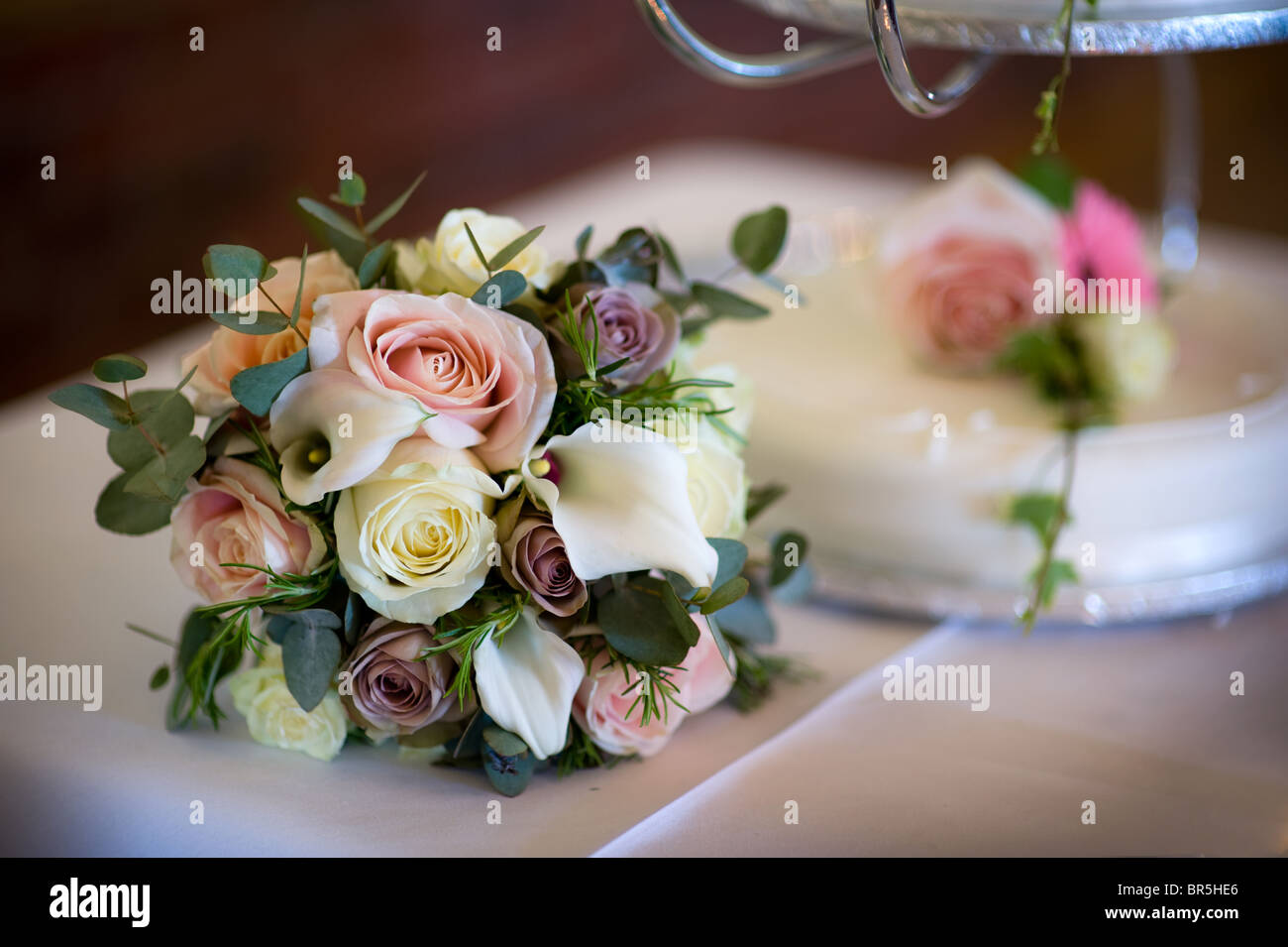 Wedding Bouquet Of Roses And Lilies On A Table Beside A Wedding Cake Stock Photo Alamy