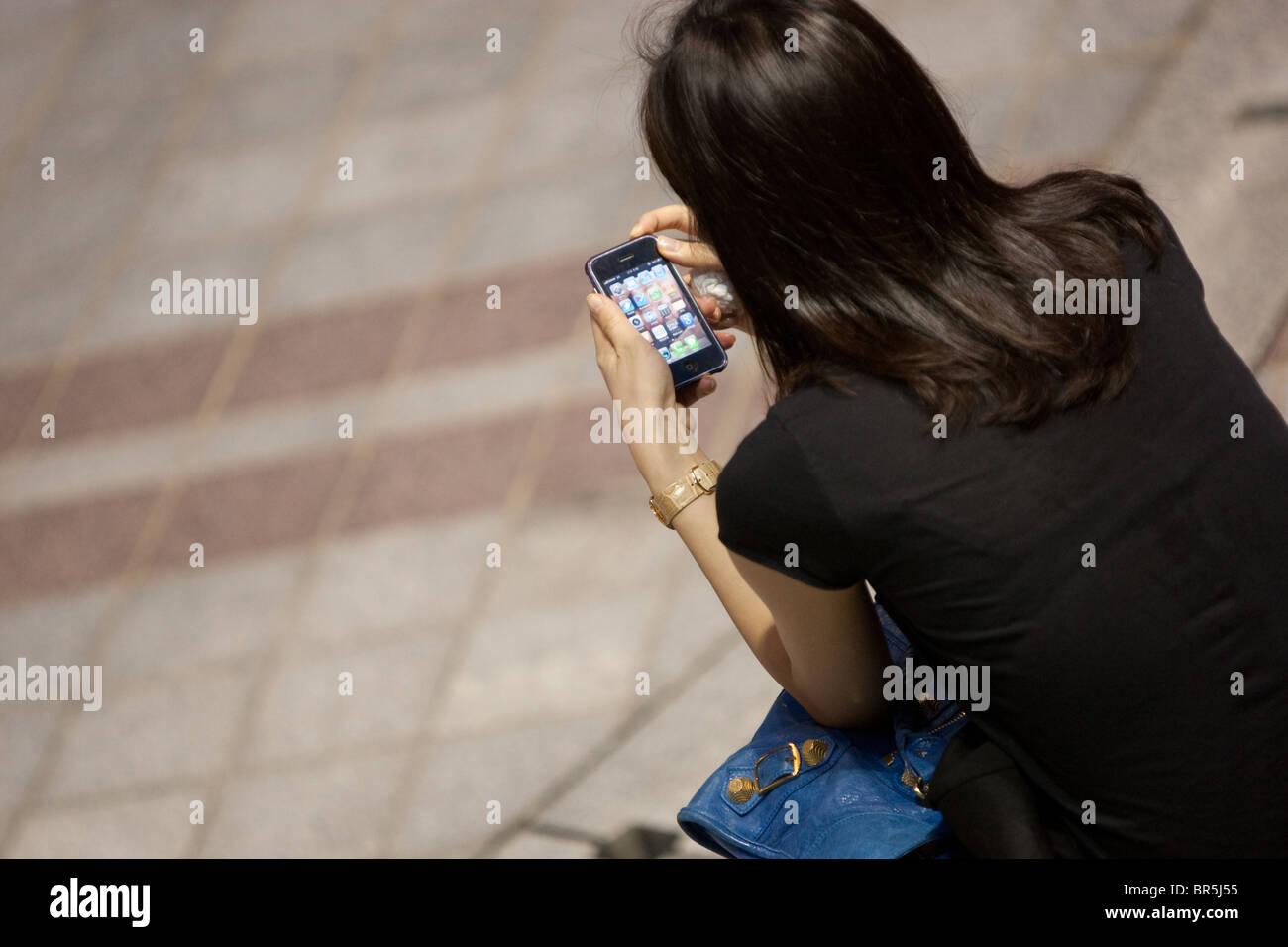 Playing with Apple Mac's iPhone outside the Shinsegae store in Namdaemun district, in Seoul, South Korea. - Stock Image