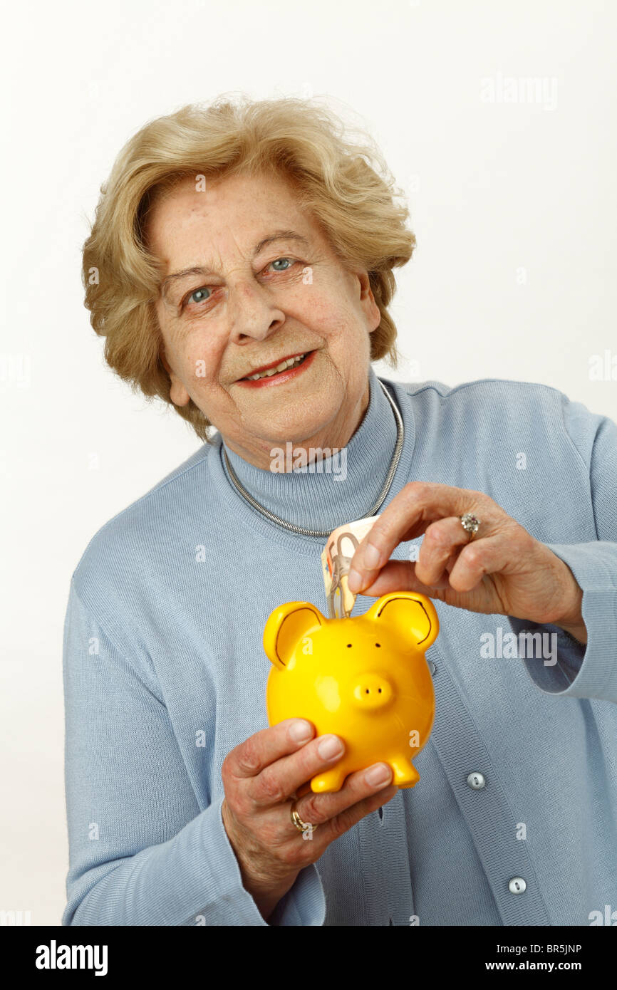 Old woman, 80 years old, holding a piggy bank - Stock Image