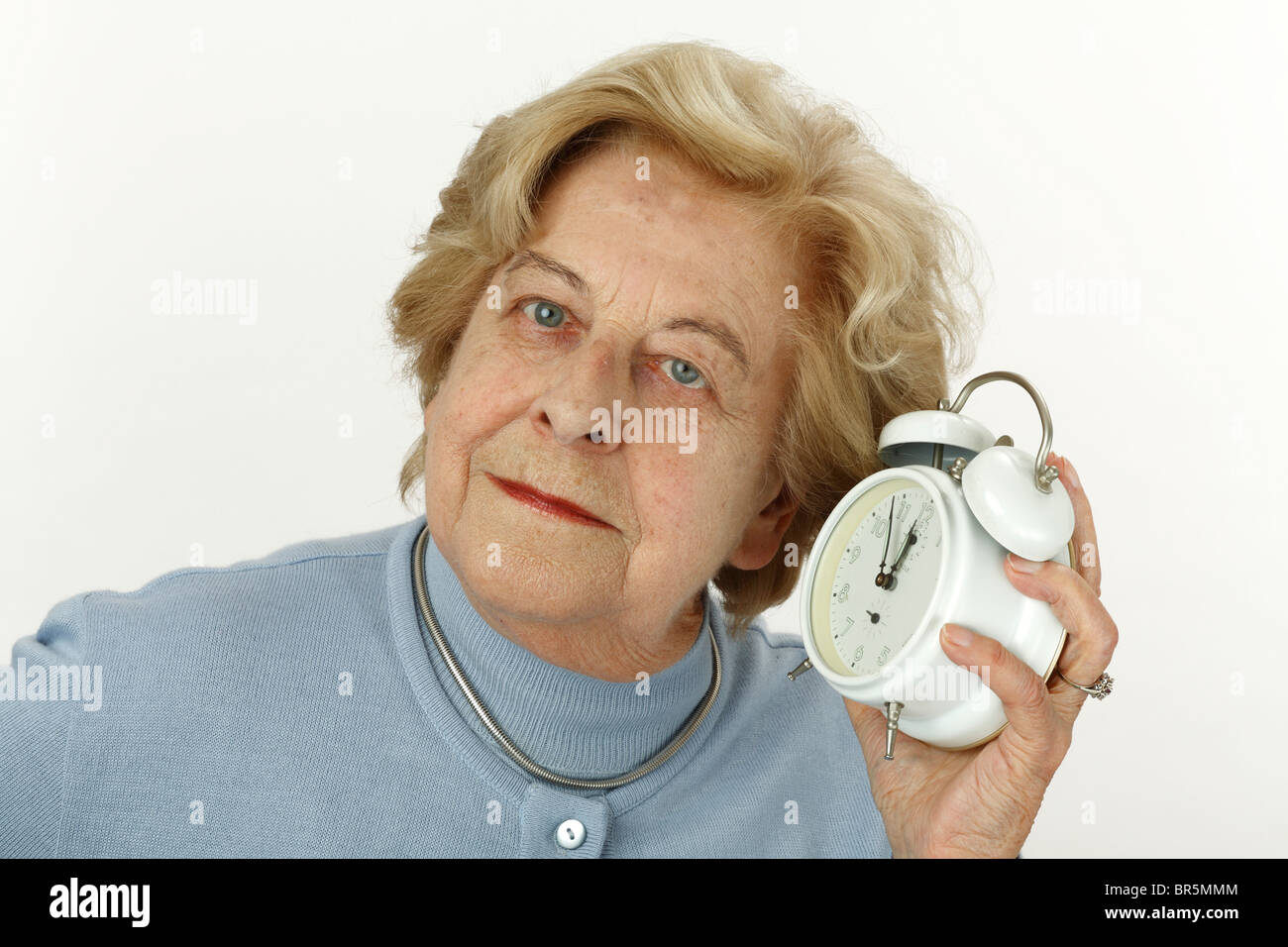 Old woman, 80 years old, holding an alarm clock, 5 to 12 - Stock Image