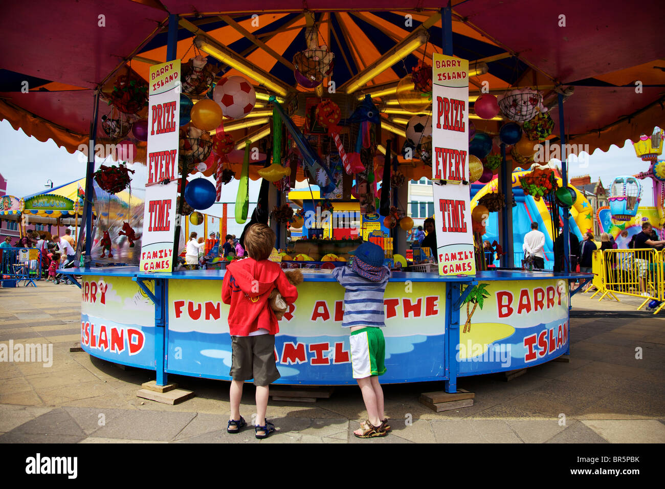 Two young boys having a go on the colourful Hook a Duck fairground stall at Barry Island - Stock Image