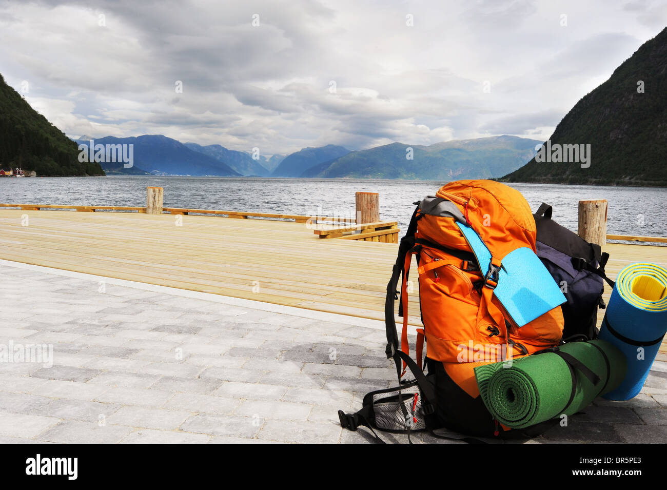 Tourists backpack on a pier in Norwagian fjords - Stock Image