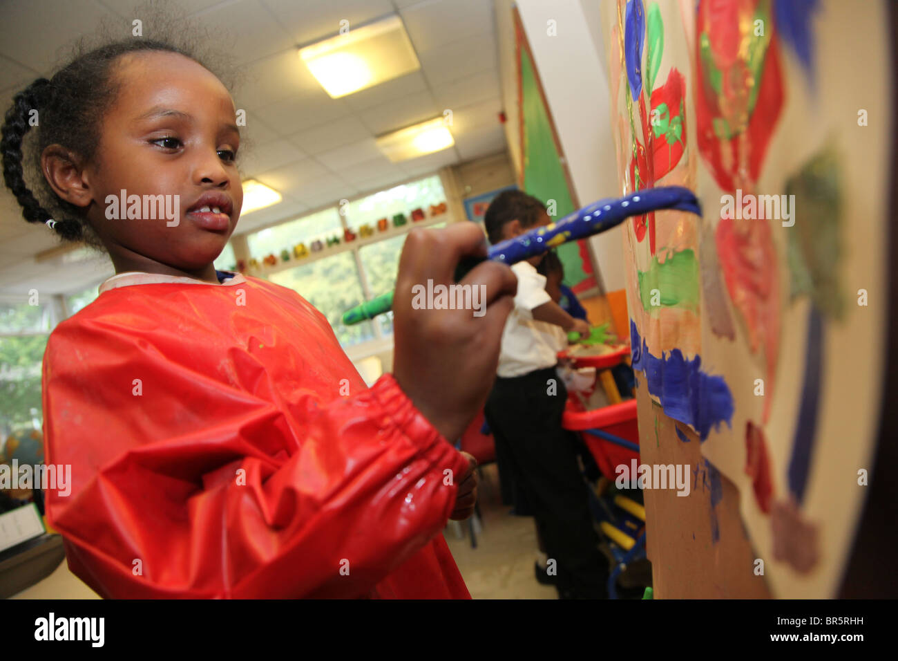 Girl painting at school. She is 5 years old, year 1 student - Stock Image