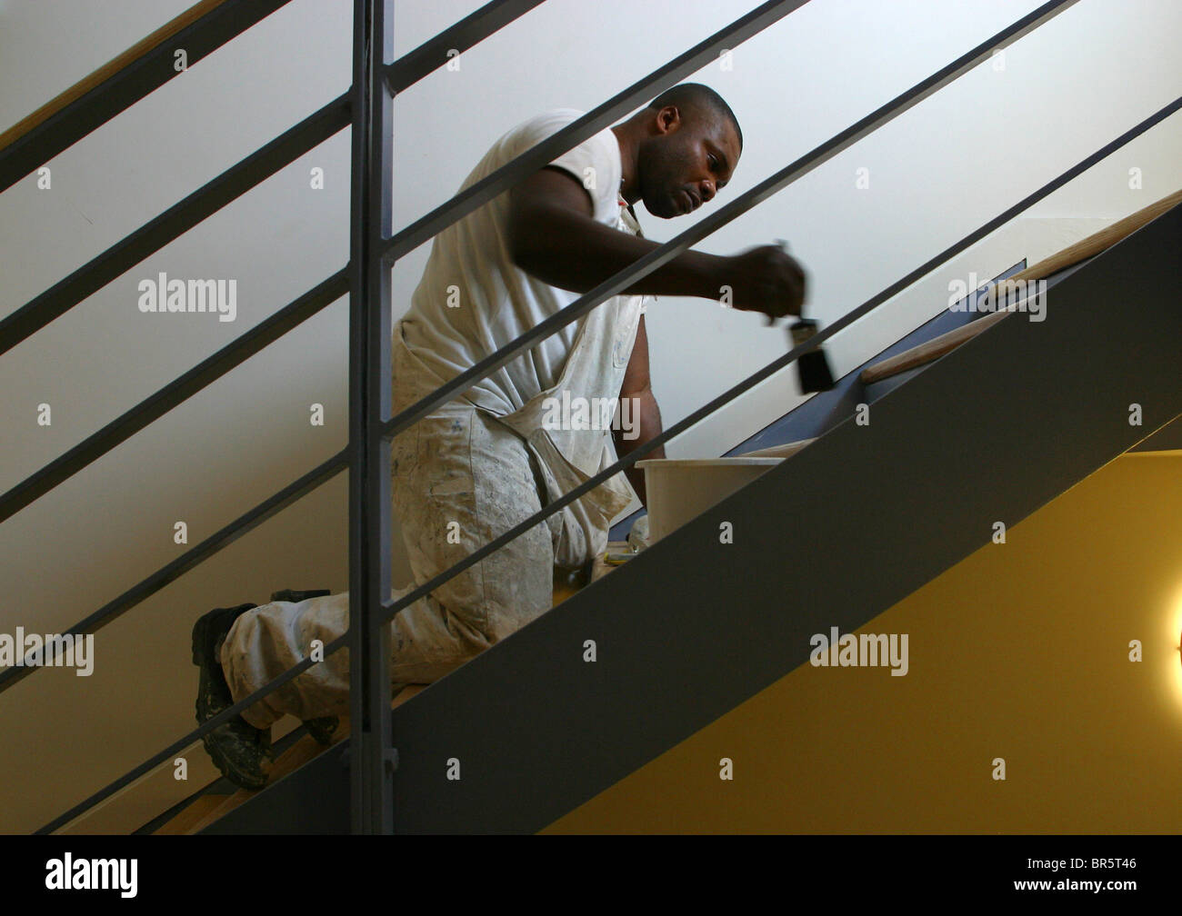 A painter and decorator varnishing each stair on a staircase inside the new East London Childcare Institute, Stratford, - Stock Image