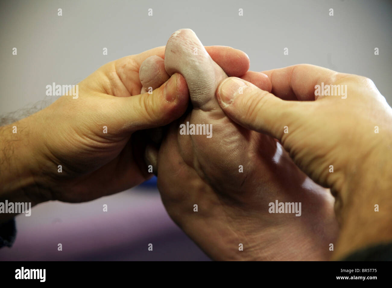 Performing an acupressure foot massage, a traditional Chinese medicine technique. - Stock Image
