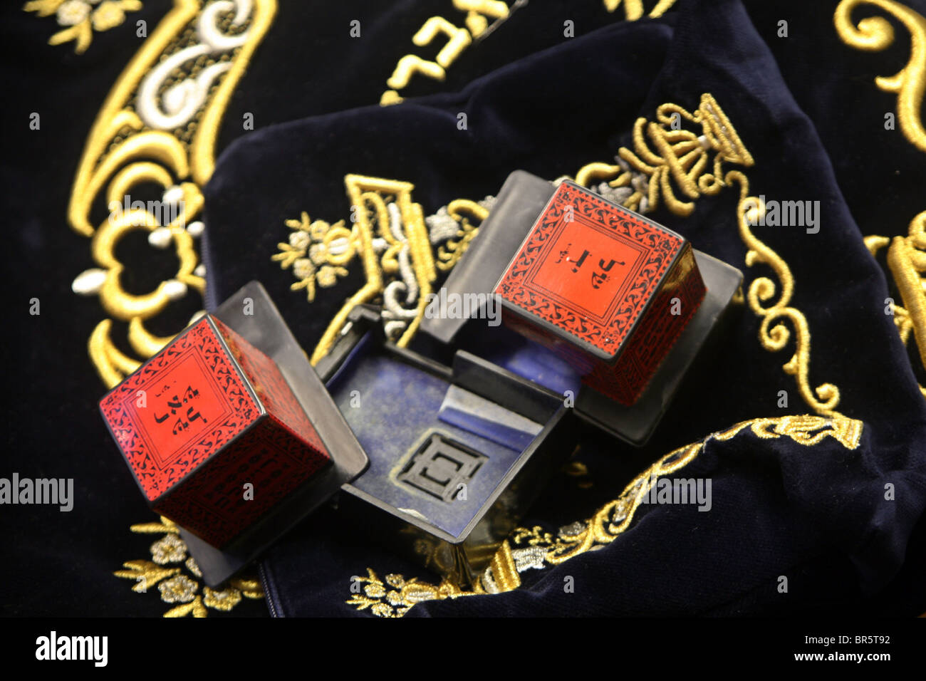 Two Tefillin cases on top of a velvet case used to protect the Tallit and siddur (prayer book containing daily prayers). - Stock Image