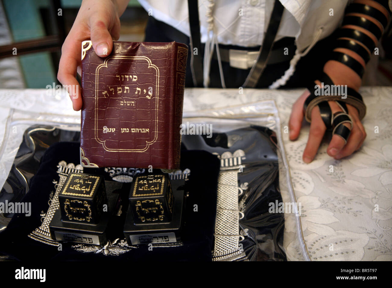 Items needed for an Orthodox Jewish man during Morning Prayer. A copy of siddur, the Tallit and two tefillins (leather - Stock Image