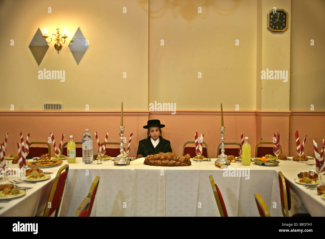 A 13 year-old Orthodox Jewish boy sits waiting for his Bar Mitzvah to begin in a Parces hall, Stamford Hill. - Stock Image