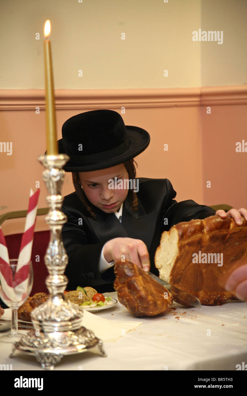 A 13 year-old Orthodox Jewish boy cuts the bread for everyone at his Bar Mitzvah meal. The Bar Mitzvah signals the - Stock Image