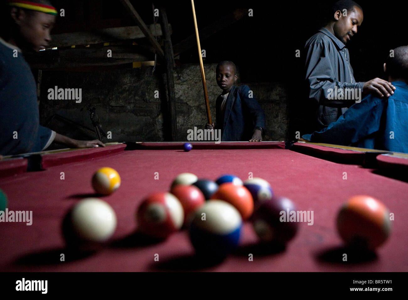 Tanzanian Street kids, play a round of pool at a local bar in Moshi. - Stock Image