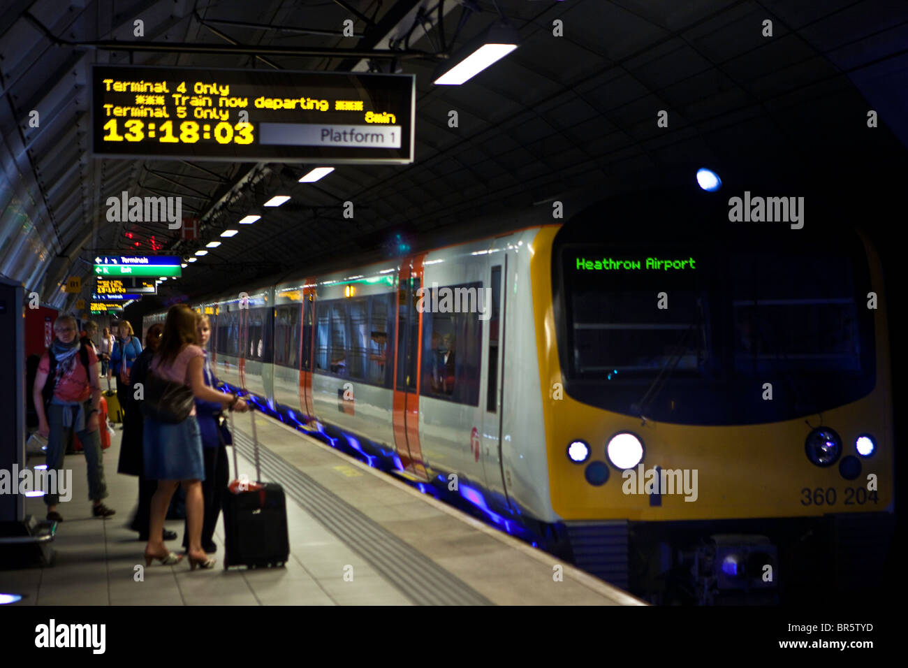 Passengers about to board the Heathrow Express train at London Heathrow Airport's Terminal 5 station. - Stock Image