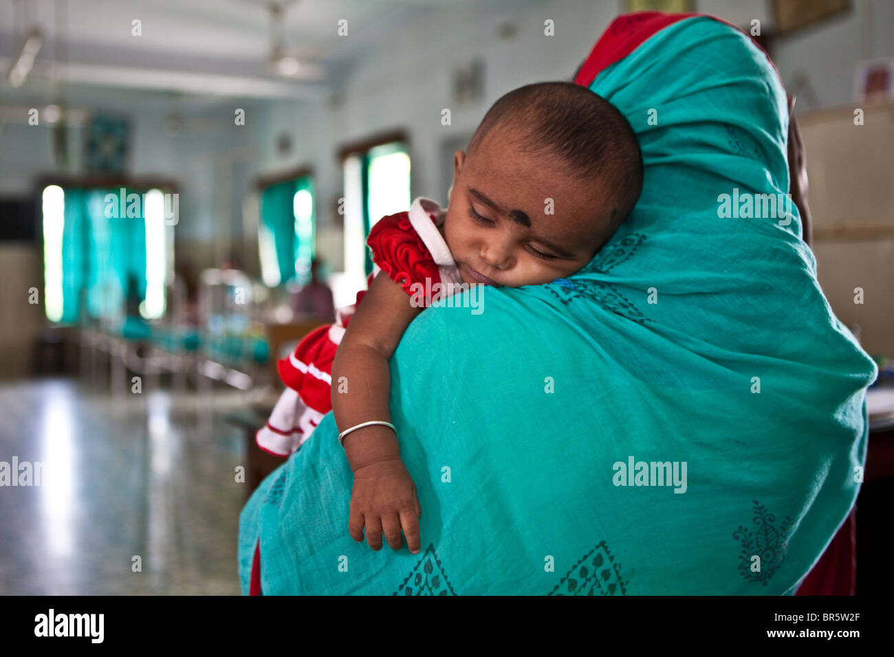 A mother brings her baby to the Child In Need Institute emergency ward. NGO led health care. - Stock Image