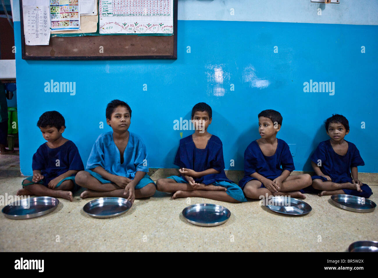 Five boys wait for their food at the CINI halfway house for vulnerable street children in Calcutta, India - Stock Image