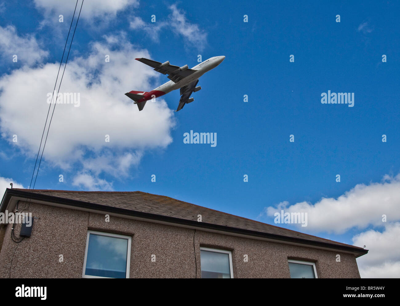 A plane taking off from London's Heathrow Airport and flying over the Hatton Cross area of Hounslow Borough. - Stock Image