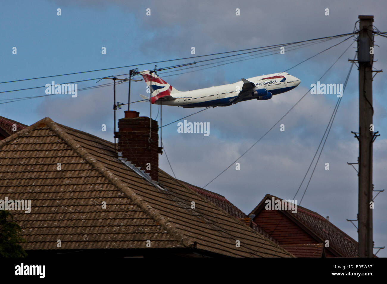 A plane taking off from London's Heathrow Airport, and flying over the Stanwell area of Hounslow Borough. - Stock Image