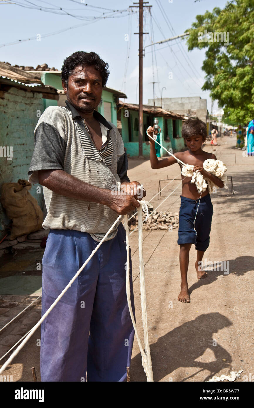 A young boy helps his father to make rope. They receive 7 rupees per Kilo of rope produced. - Stock Image
