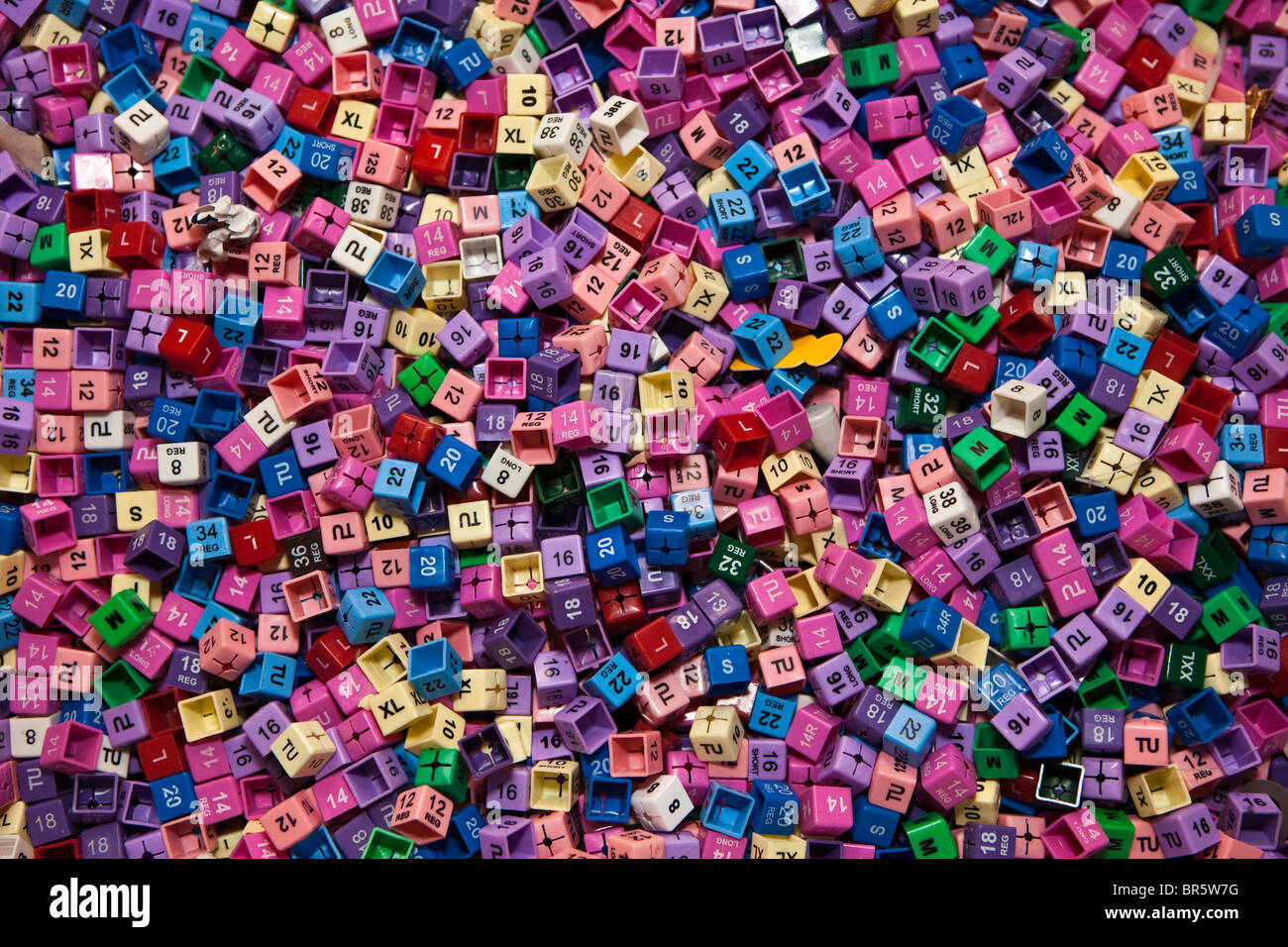 Hundreds of plastic clothes tags, showing all the sizes and different colour codings. - Stock Image