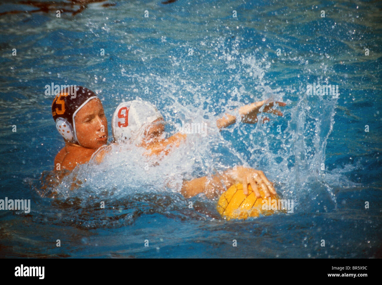 High school water polo player team ball splash swim pool charge aggressive stop prevent - Stock Image