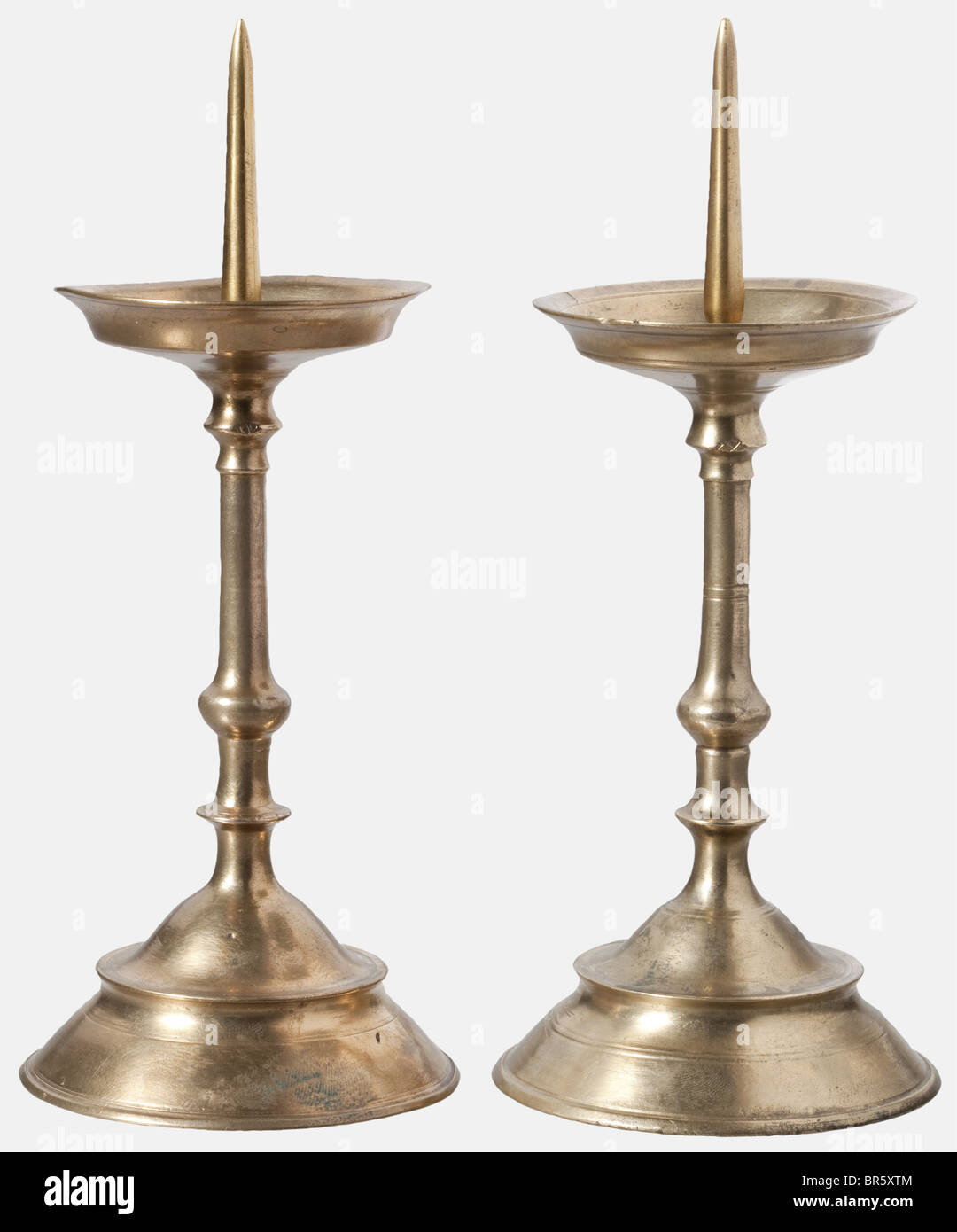 A pair of candle holders, Nuremberg, circa 1600 Brass holders cast in one piece with bell-shaped feet, slender stems - Stock Image
