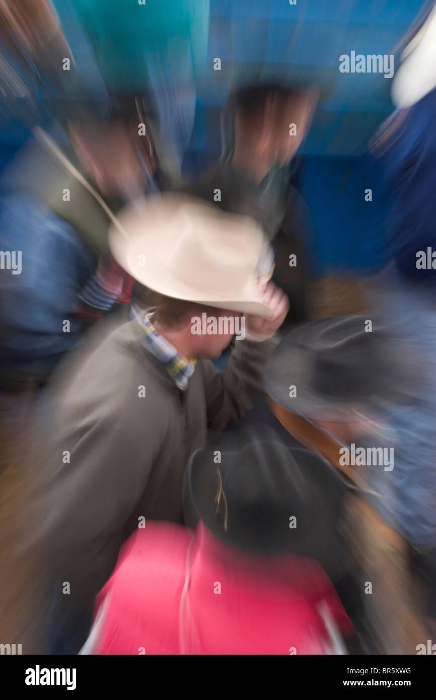 Zoomed exposure of cowboys waiting - Stock Image