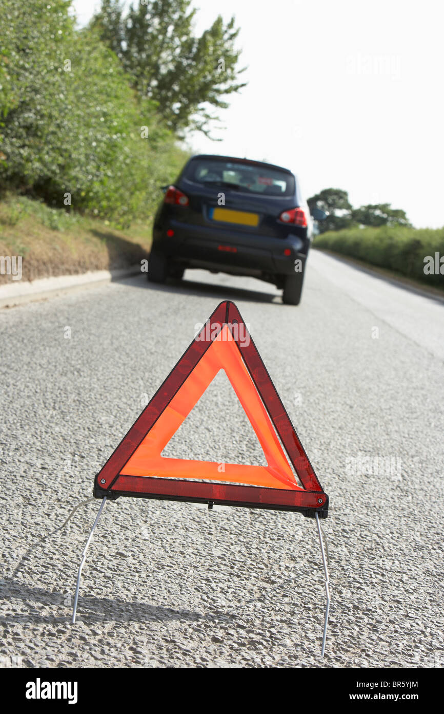 Car Broken Down On Country Road With Hazard Warning Sign In Foreground - Stock Image