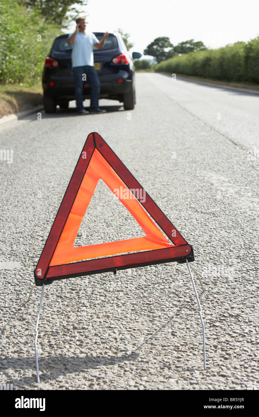Driver Broken Down On Country Road With Hazard Warning Sign In Foreground - Stock Image