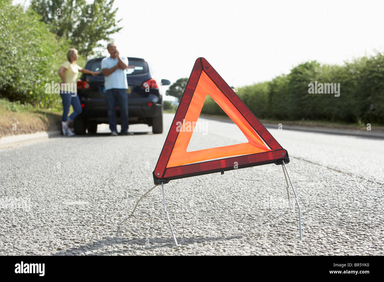 Couple Broken Down On Country Road With Hazard Warning Sign In Foreground - Stock Image