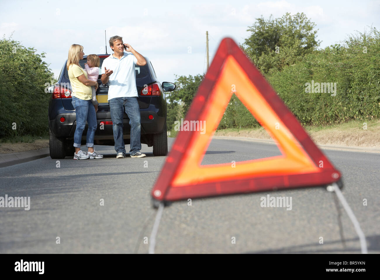 Family Broken Down On Country Road With Hazard Warning Sign In Foreground - Stock Image