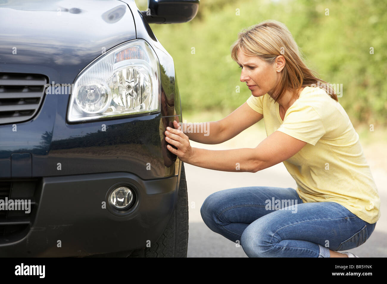Female Driver Broken Down On Country Road - Stock Image