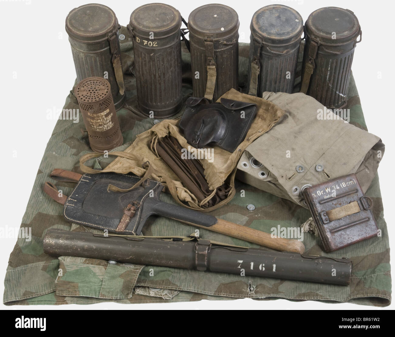 A group of Wehrmacht equipment, including five feldgrau painted gasmask carriers (some with a roll number), a black - Stock Image