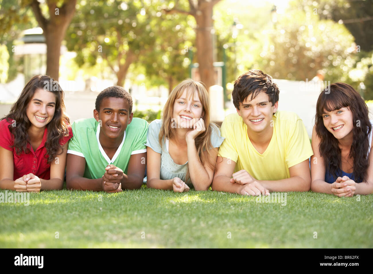 Group Of Teenagers Lying On Stomachs In Park - Stock Image