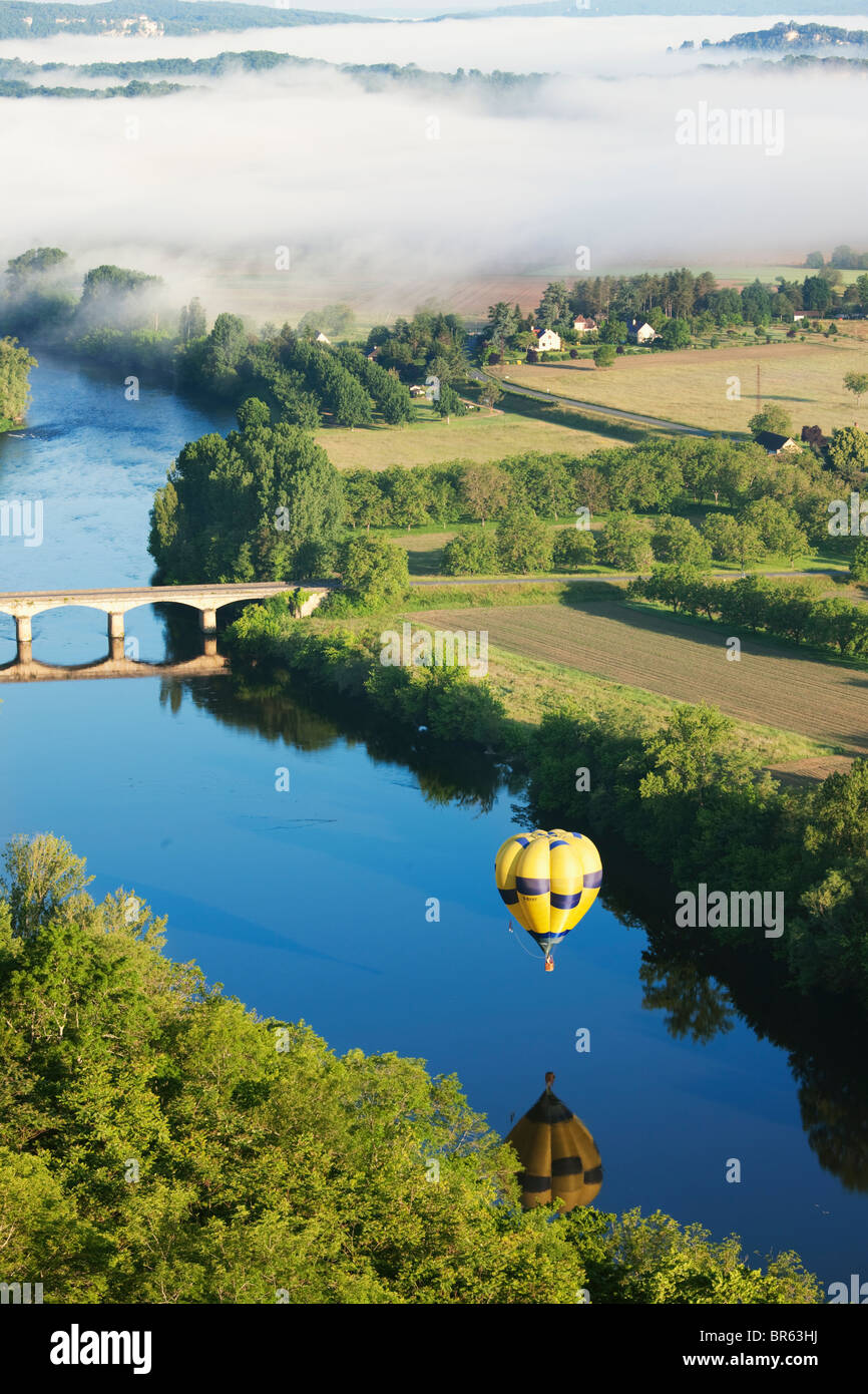 Hot air balloon and morning mist over the river Dordogne; France Stock Photo