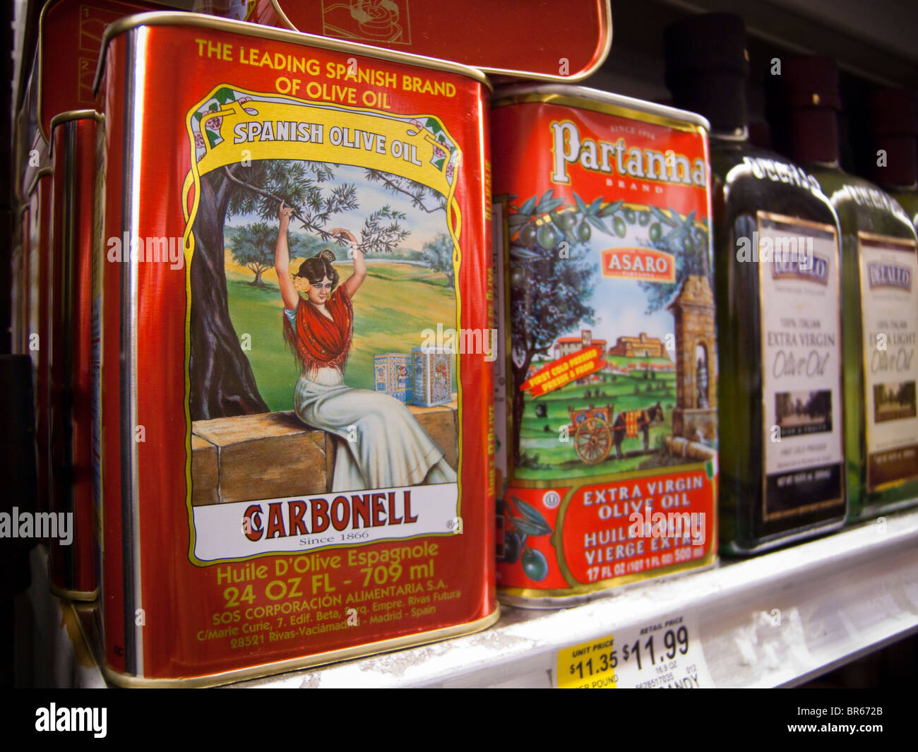 Cans of imported olive oil including Spanish are seen on a supermarket shelf - Stock Image
