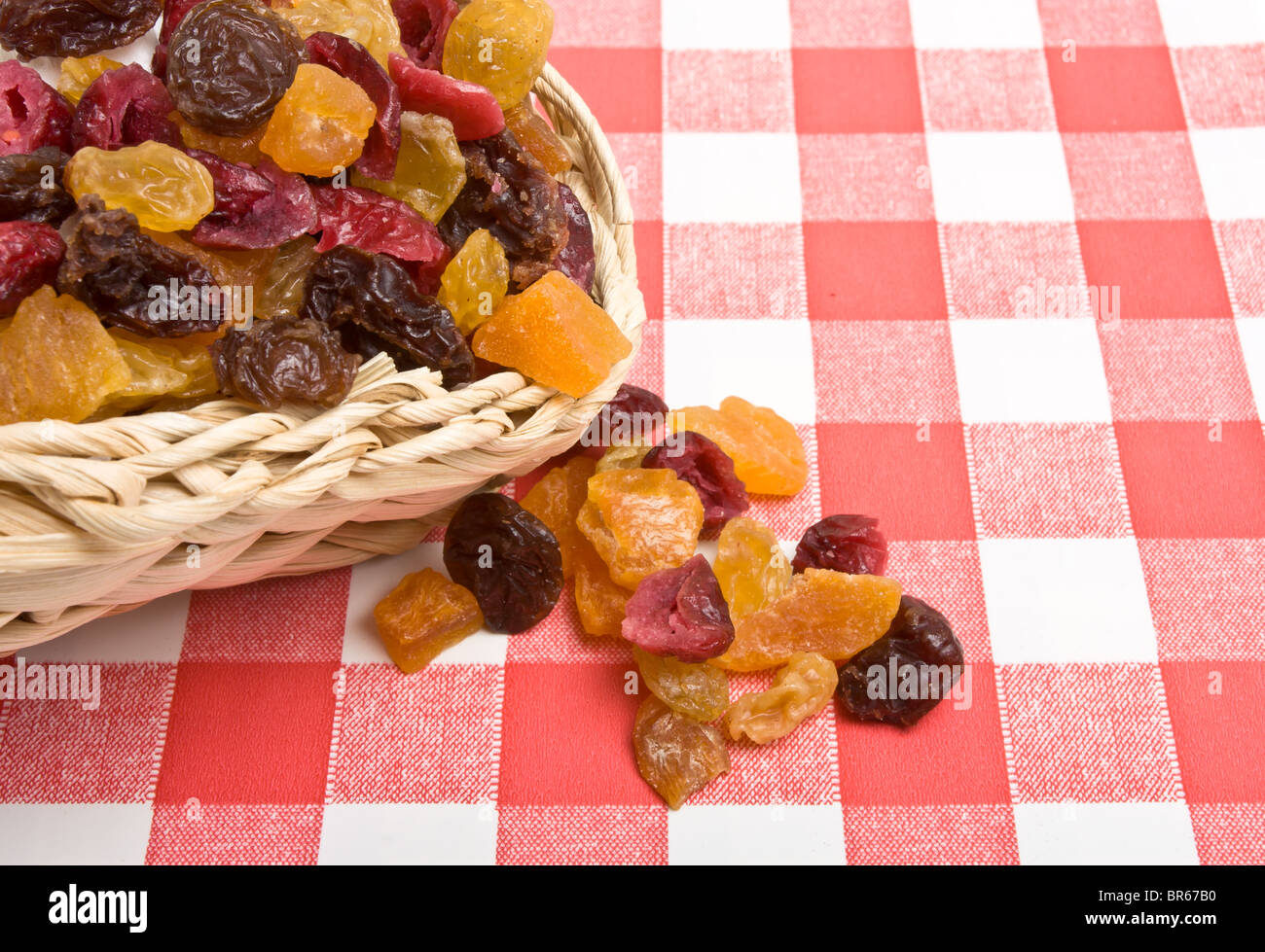 Dried Fruits of apricot, sultana, raisins and cranberries spilling onto red and white tablecloth. - Stock Image