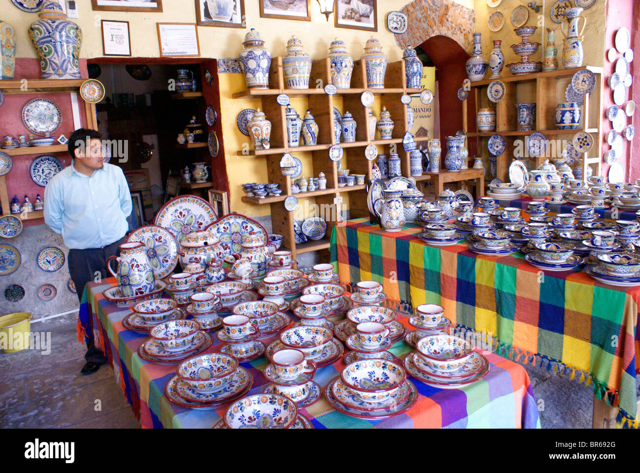 Clerk in a shop selling colorful Talavera pottery in the city of Puebla, Mexico - Stock Image